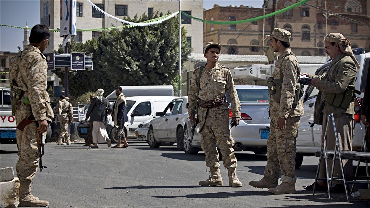 Des gardes chiites Houthis vêtus d'uniformes militaires font le guet dans une rue menant au palais présidentiel à Sanaa, la capitale, mercredi le 21 janvier 2015.