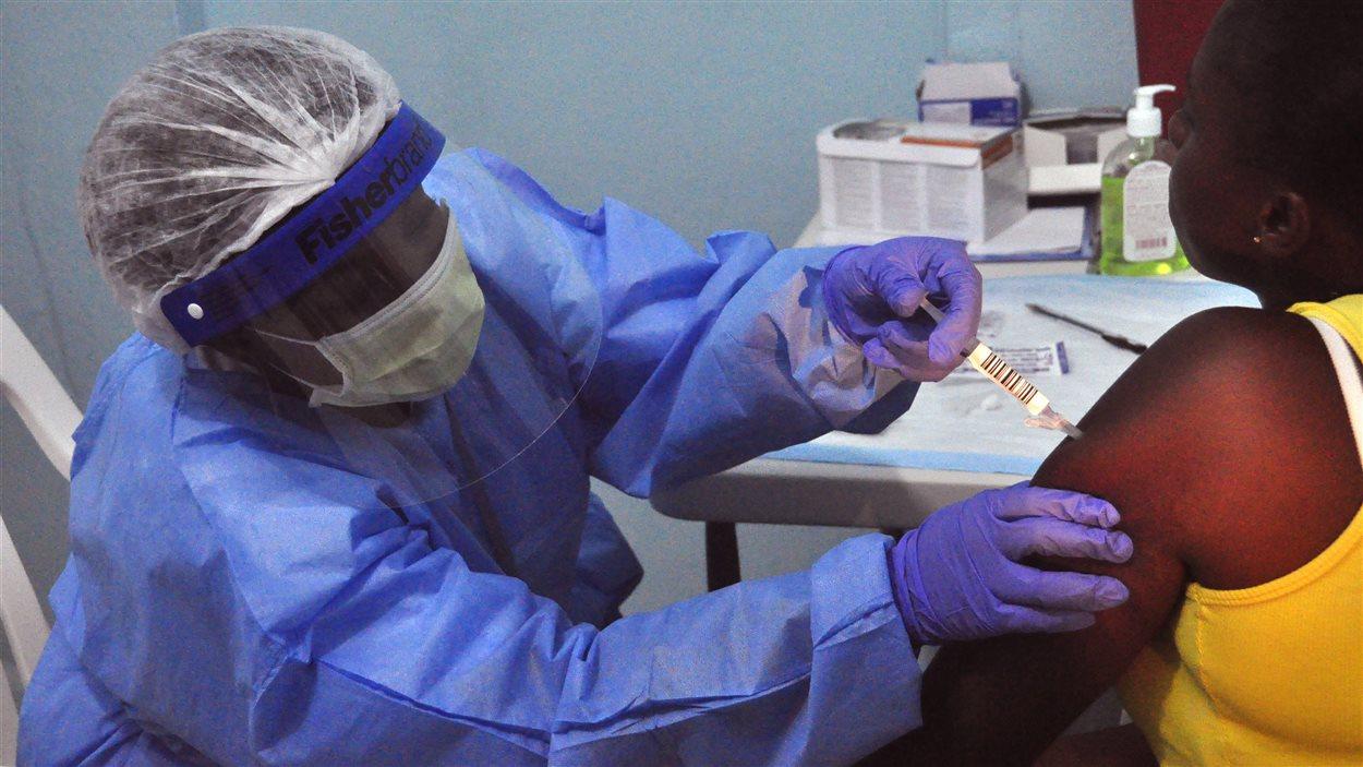 Une femme se fait donner un vaccin dans un hôpital du Libéria, lundi.