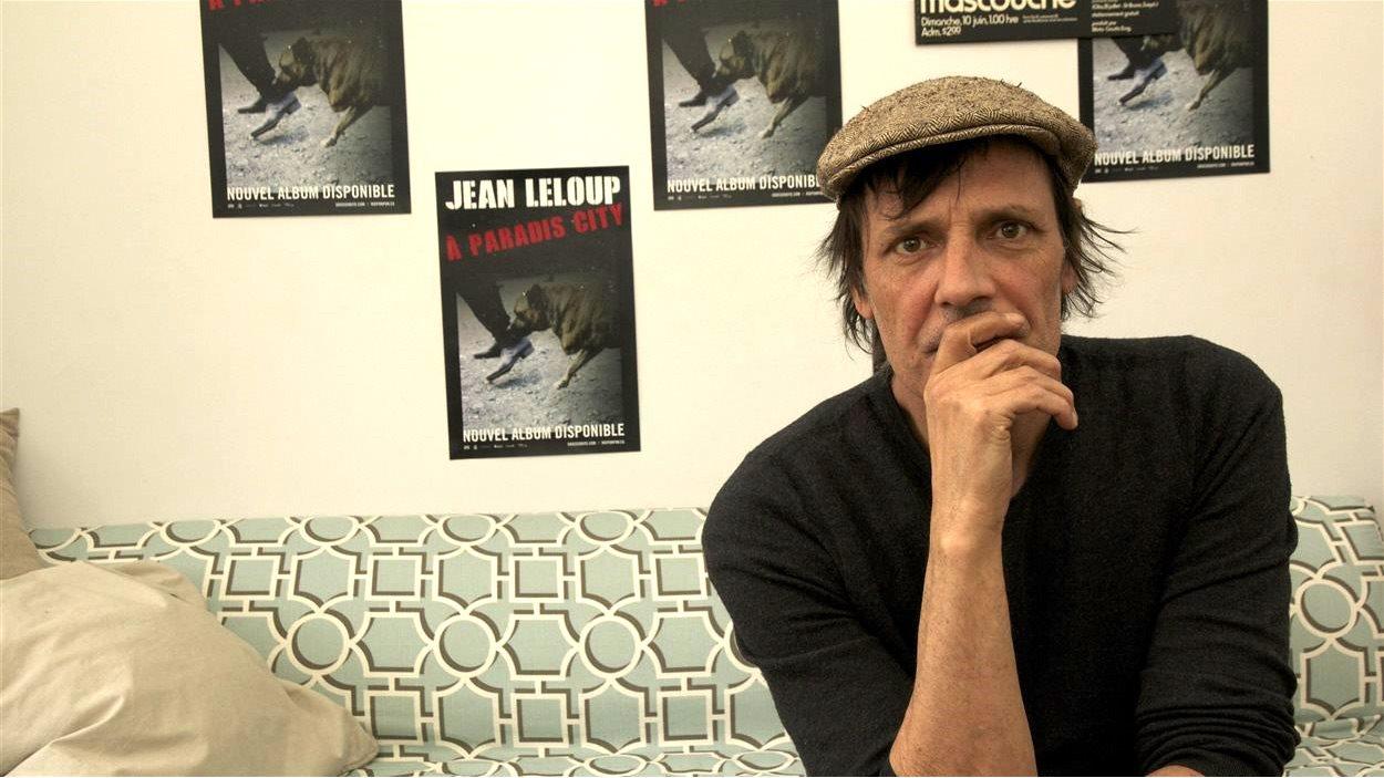 Jean Leloup songeur devant les affiches de son dernier album : À Paradis City