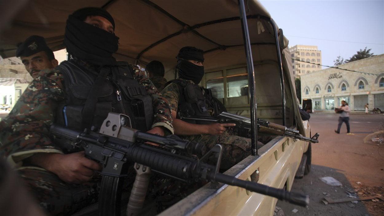 Des combattants houthis en tenue de policiers près du palais présidentiel à Sanaa