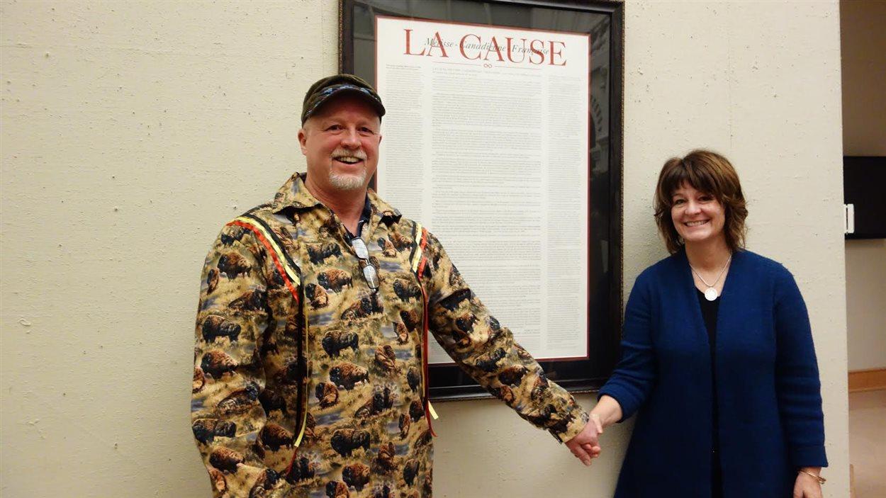 Brad Mix et sa femme Susan devant la reproduction du pamphlet «La Cause» rédigé par son ancêtre, Charles Sauvé, en 1908.