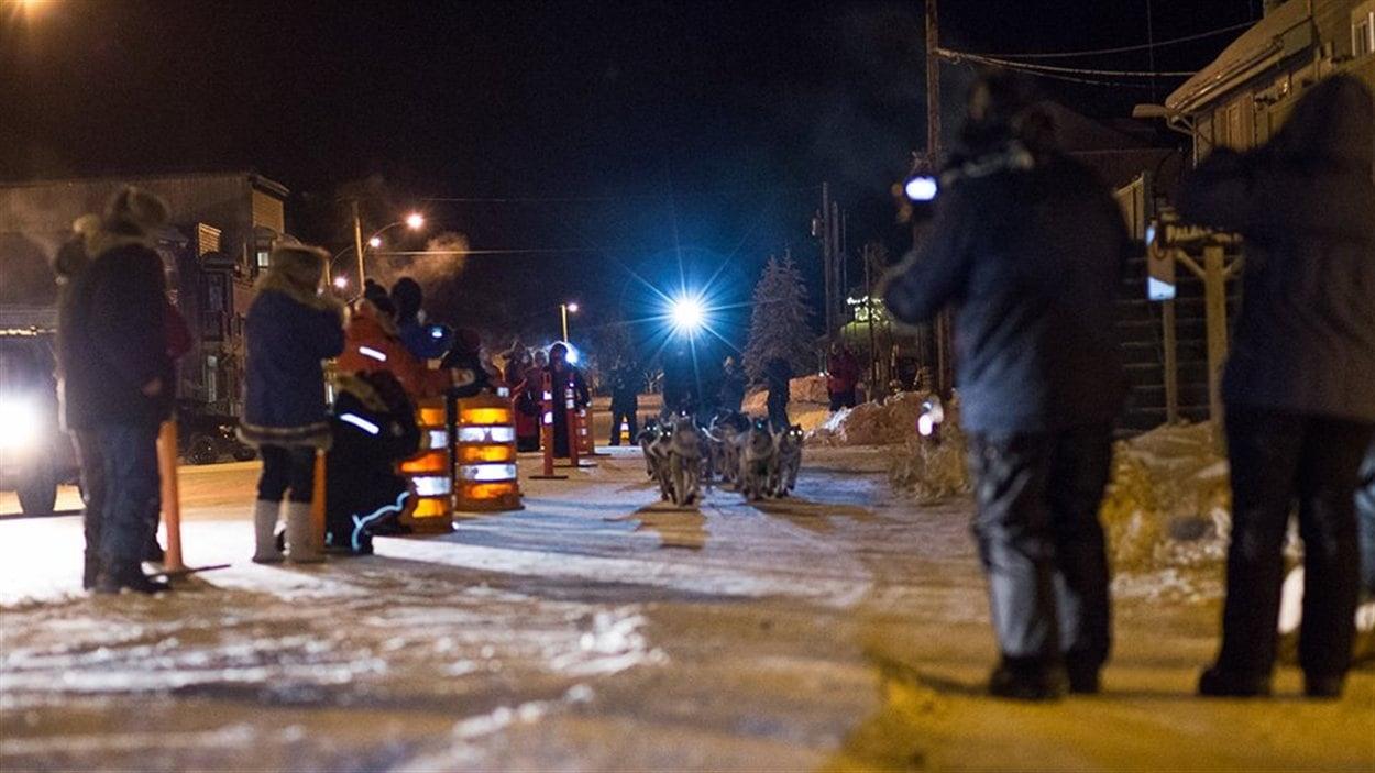 Une équipe de trapineau à chiens arrive à Dawson City de nuit.