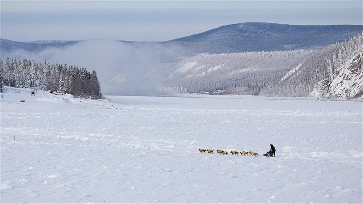 Une équipe traverse le fleuve Yukon en face de Dawson City vers les sites de campement.