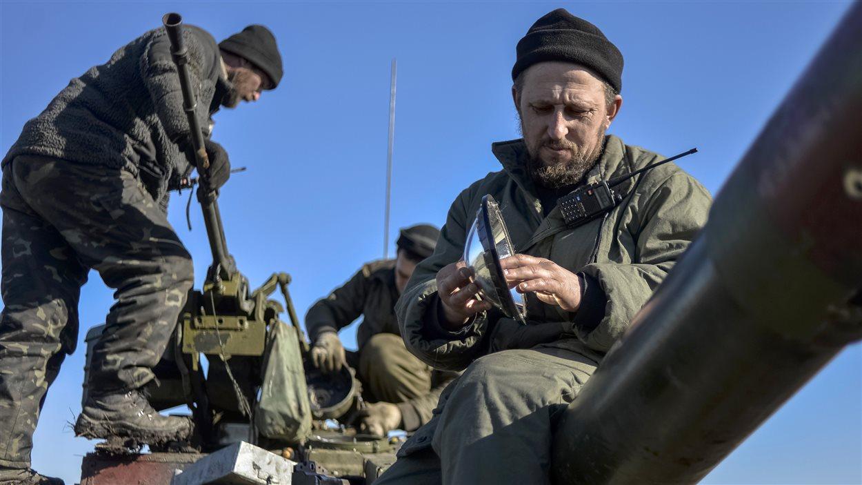 Des soldats ukrainiens s'occupent de leur équipement sur un char d'assaut à Donetsk.