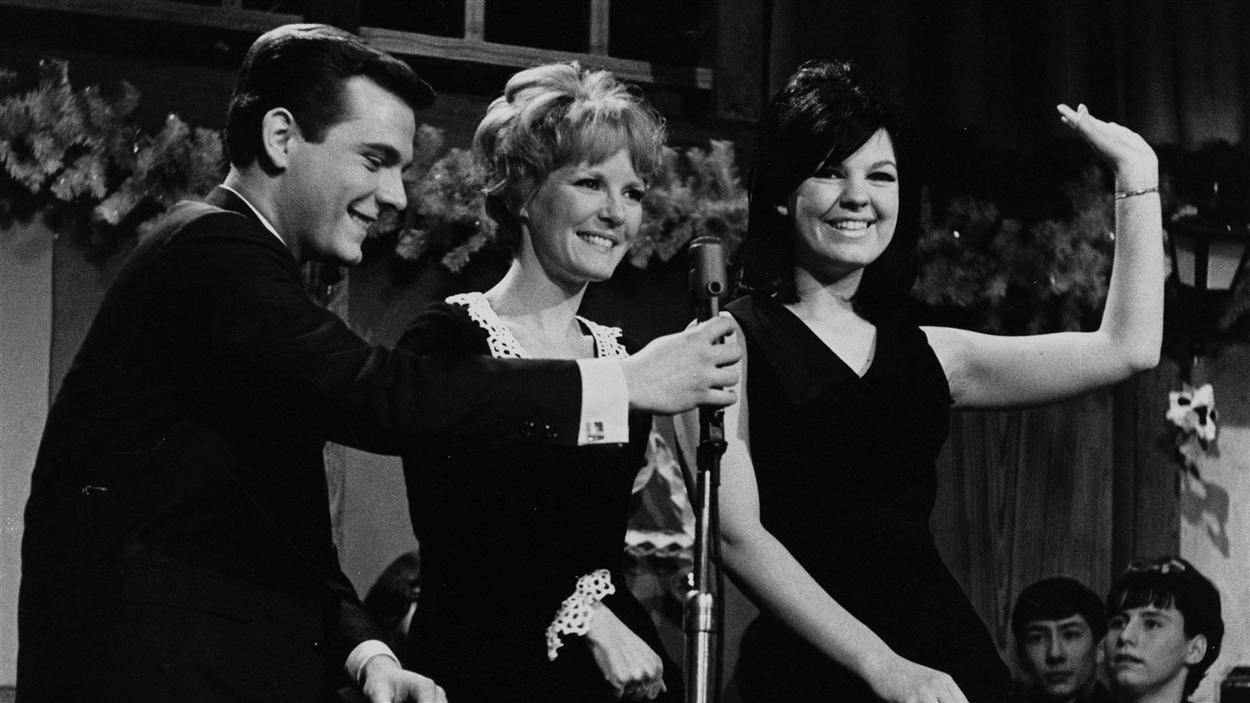 L'animateur Pierre Lalonde tient le micro devant les chanteuses Petula Clark et Michèle Richard, en 1966.