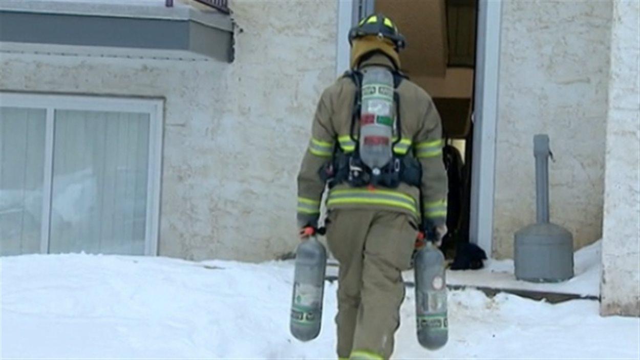 Un pompier entrant dans l'immeuble où cinq enfants et leur mère ont été empoisonnés par un pesticide utilisé pour éradiquer des punaises de lit.