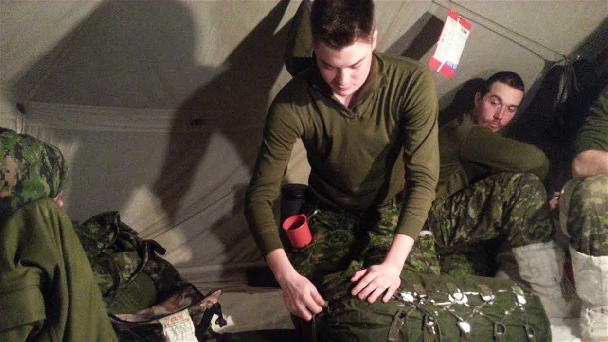 Un militaire a mis en place un petit matelas isolant pour dormir sur la neige. Il installe maintenant son sac de couchage.