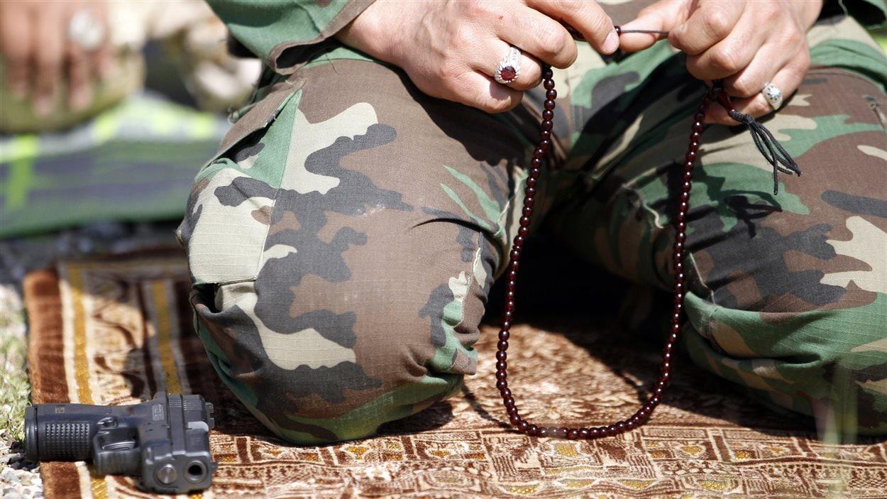 Un combattant chiite a déposé son arme pour prier, en prévision de l'offensive sur Tikrit.