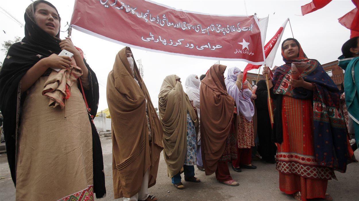 Manifestation au Pakistan : les femmes tiennent une affiche sur laquelle elles prônent l'élimination de toute barrière politique, sociale et économique qui asservissent les femmes.