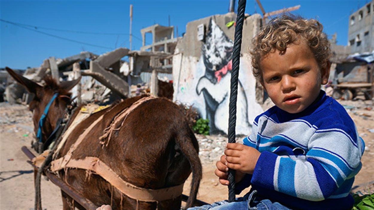Un enfant devant une oeuvre de Banksy, dans la bande de Gaza