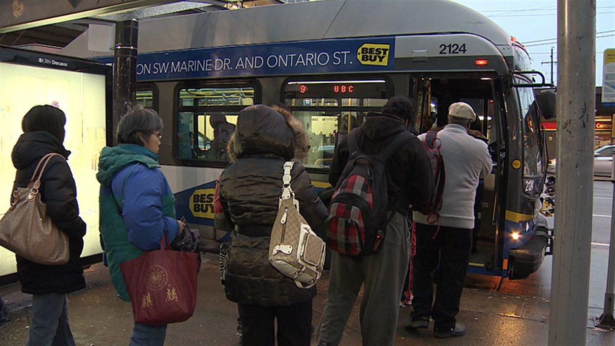 Des passagers attendent de monter dans l'autobus à Vancouver