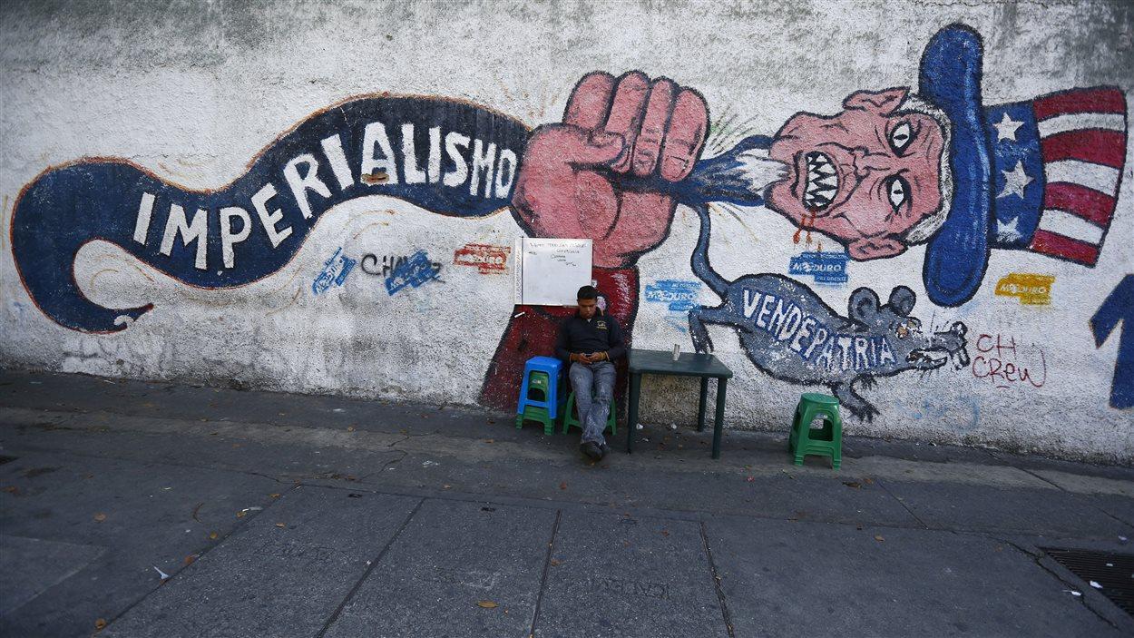 À Caracas, un homme est assis devant un graffiti représentant les États-Unis, et sur lequel on peut lire les mots «Impérialisme» et «Traître».