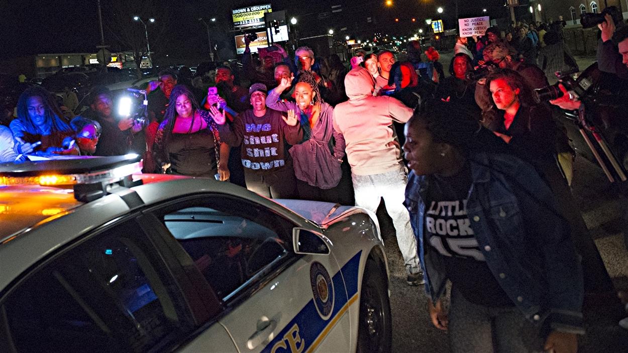 Des manifestants empêchent une voiture de police de circuler