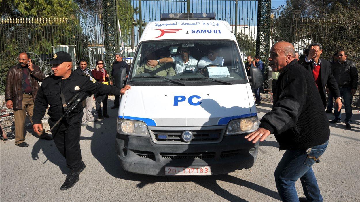 Des membres des forces de l'ordre protègent une ambulance sur les lieux de l'attentat.