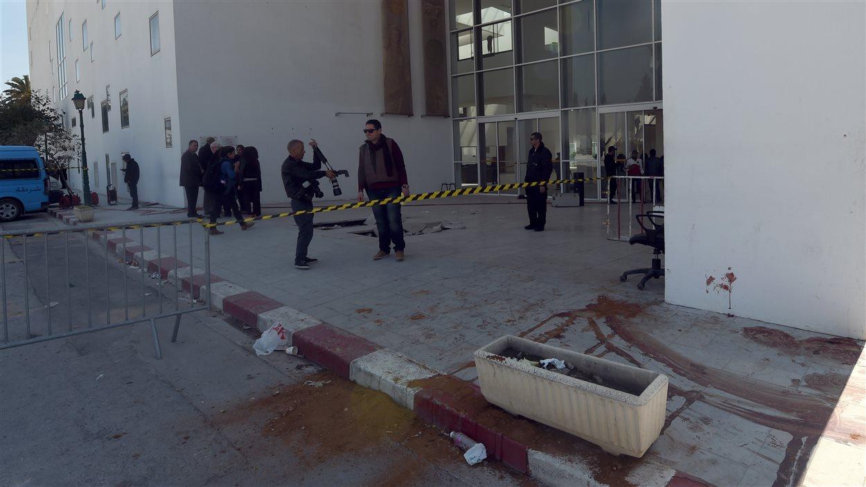 Des membres des forces de sécurité et des journalistes, devant le musée du Bardo, jeudi matin. Des traces du drame de la veille sont toujours bien visibles.