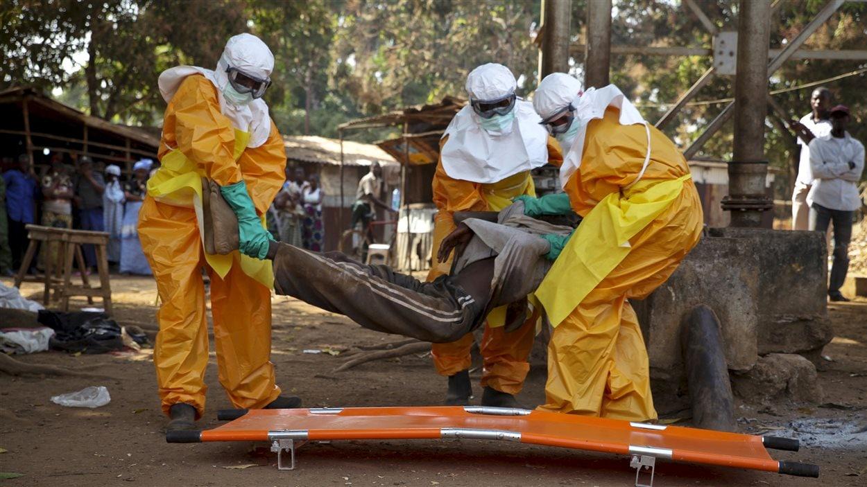 Une équipe de la Croix rouge transporte un homme qu'on suspecte d'être une victime de l'Ebola à Forecariah, en Guinée.