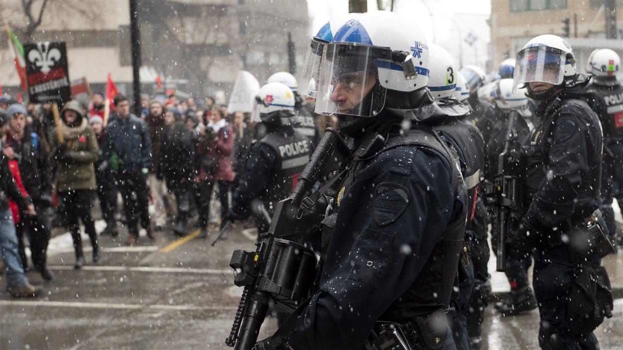 Des policiers surveillent la manifestation contre l'austérité à Montréal.