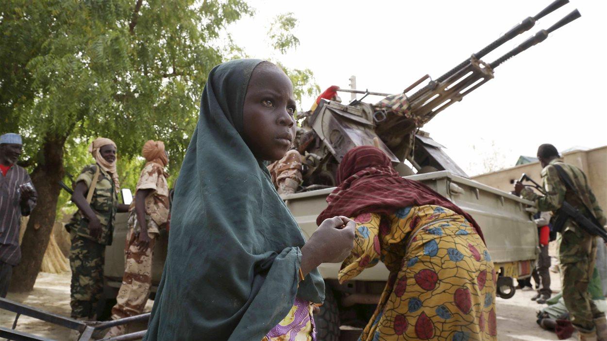 Une fillette se tient devant des soldats du Niger et du Tchad dans la ville de Damasak, qui vient d'être reprise à Boko Haram.