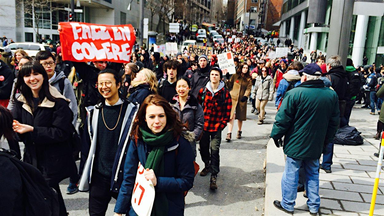 Des étudiants déambulent dans le centre-ville de Montréal, dans le cadre d'une manifestation contre l'austérité et contre l'exploitation des hydrocarbures.