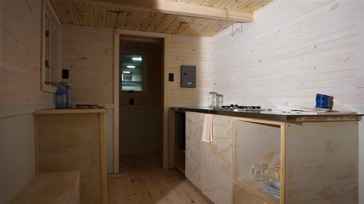 Lorsqu'on entre dans la maison, on accède d'abord à la cuisine, et au fond, on retrouve la salle de bain.