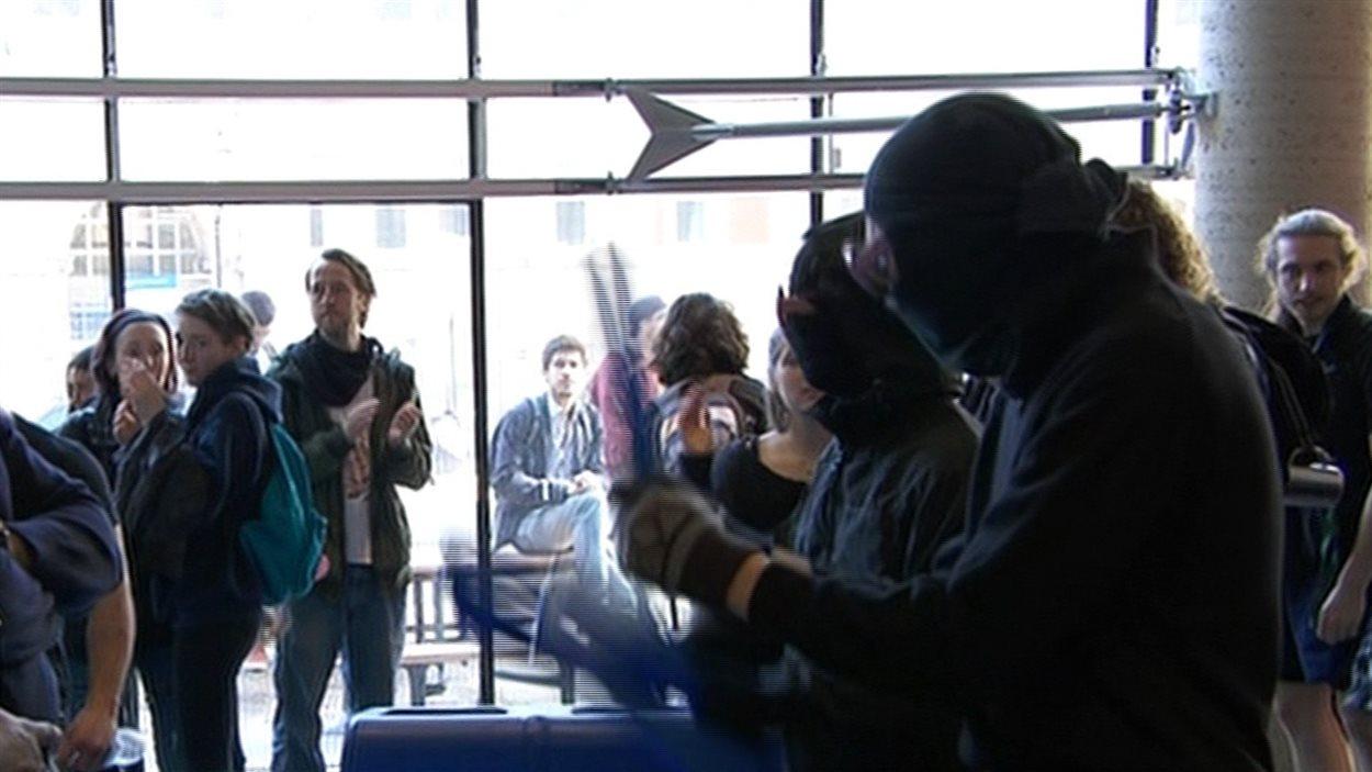 Des manifestants masqués frappent sur des poubelles.