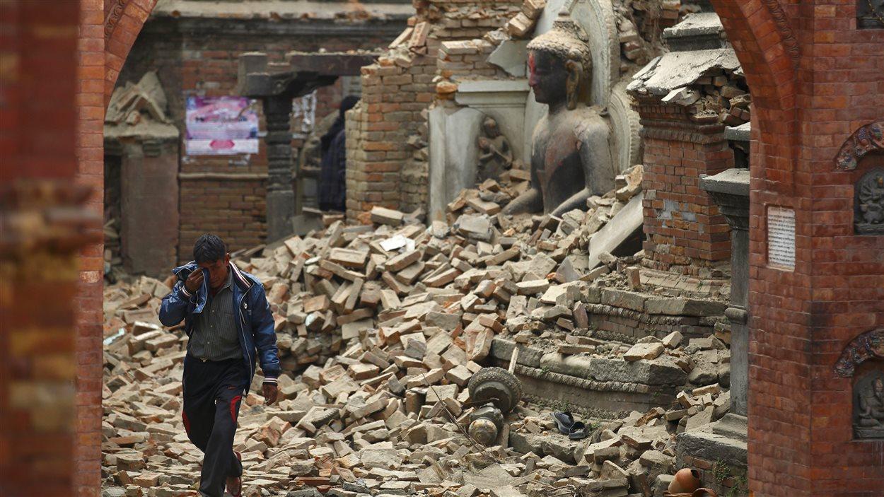 Au Tibet, des secouristes aident une femme à regagner la terre ferme après le séisme.