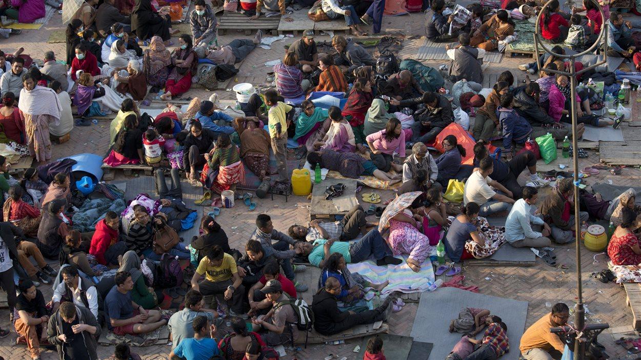 Des Népalais installés dans une aire ouverte pour rester en sécurité malgré les secousses.