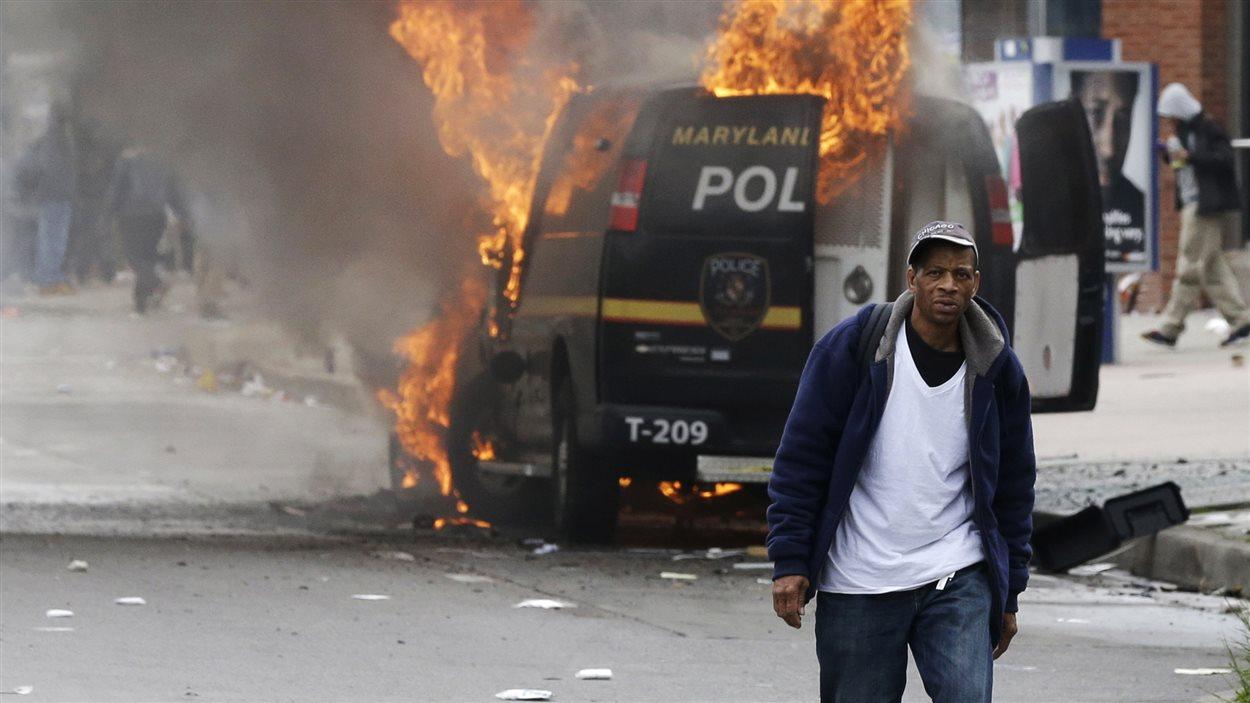 À Baltimore, un passant marche près d'un véhicule de police incendié dans la foulée des émeutes ayant éclaté après les funérailles de Freddie Gray.