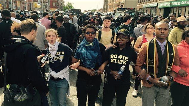 Une chaîne humaine de bénévoles s'est formée entre les manifestants et les policiers à Baltimore, pour éviter tout contact.