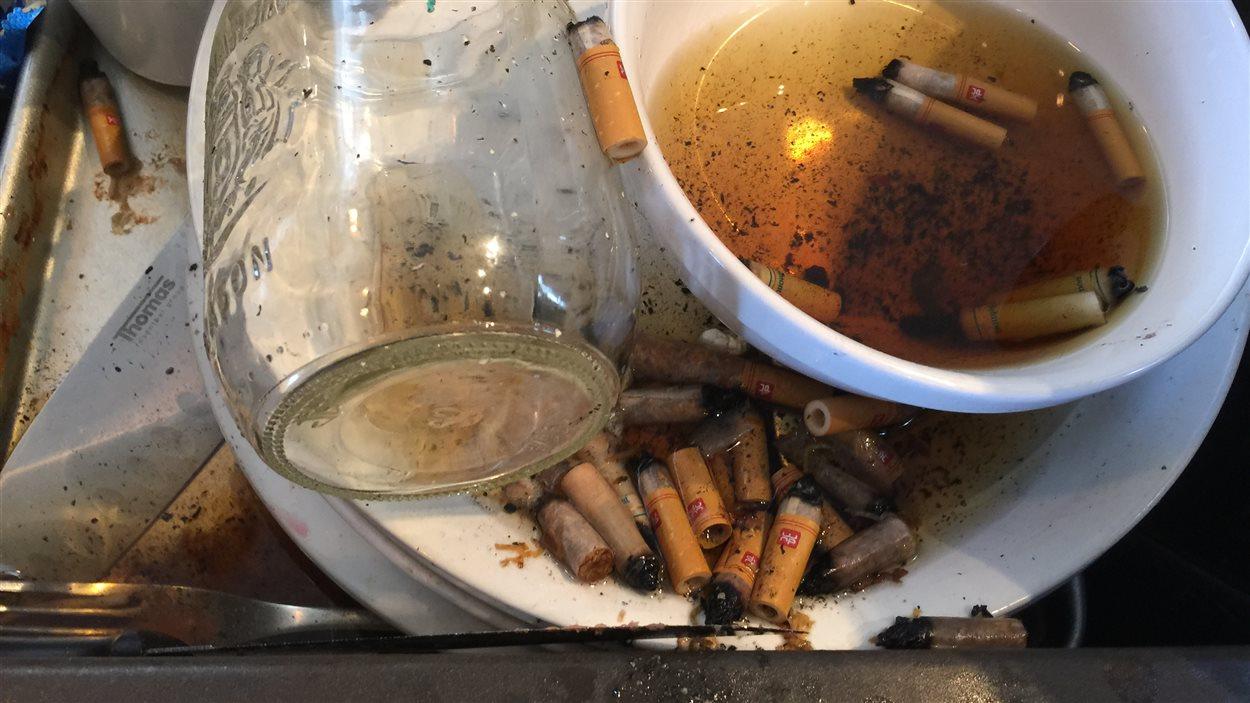 Des mégots de cigarette et de la vaisselle sale