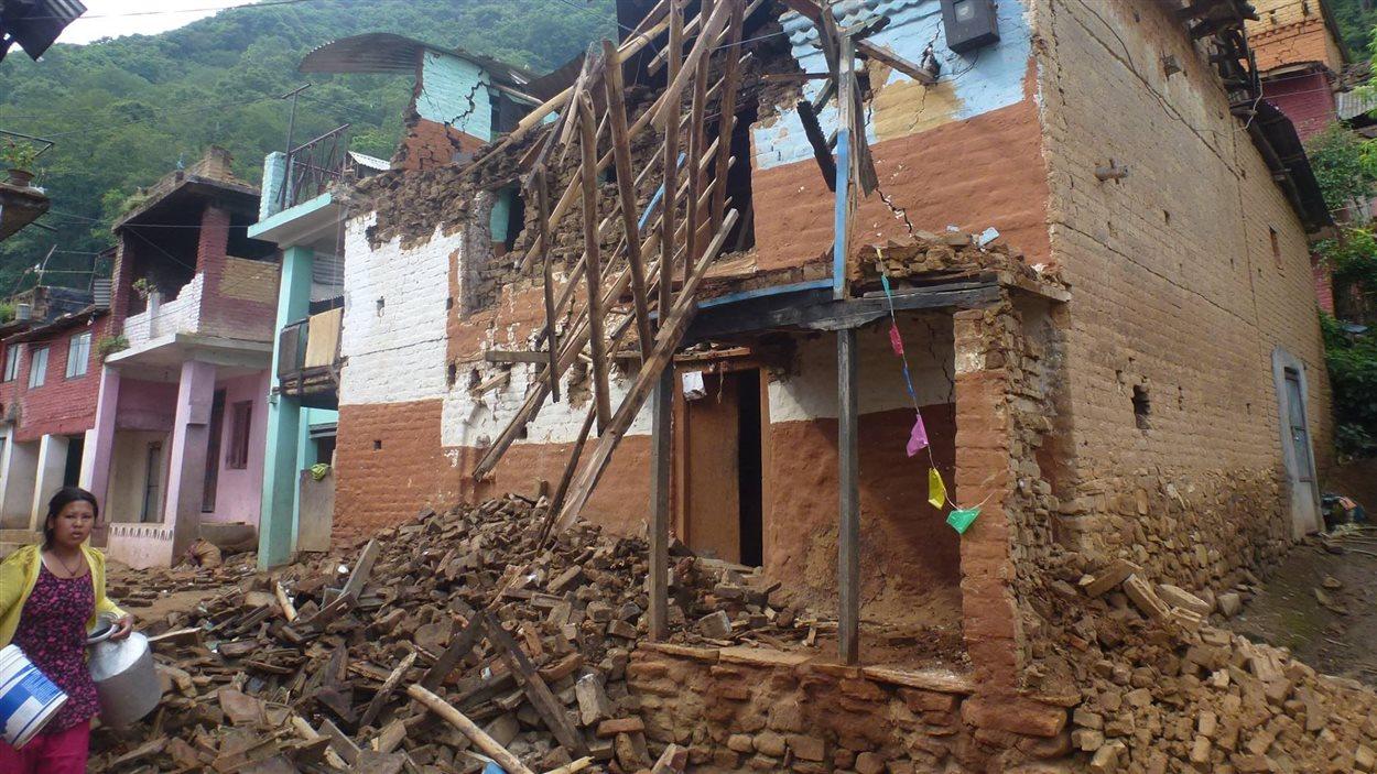 Maison détruite dont les débris ont recouvert la rue.