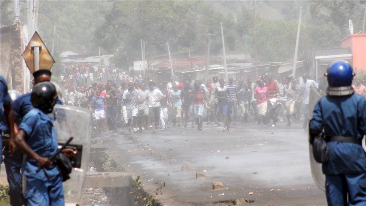Des policiers de l'escouade anti-émeute observent les manifestants qui militent contre la nouvelle candidature du président du Burundi.