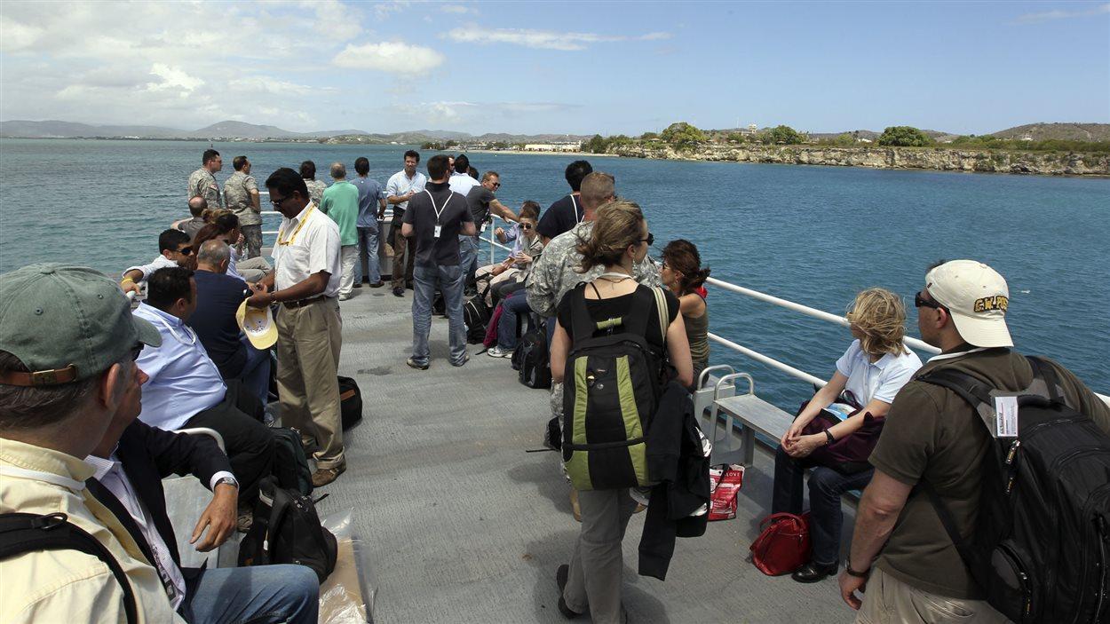 Des journalistes à bord d'un traversier les transportant vers Guantanamo Bay lors du procès de Khalid Sheik Mohammed, en 2012.