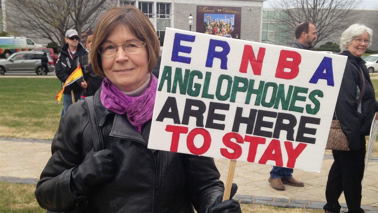Manifestation contre le bilinguisme à Fredericton. «Les anglophones sont ici pour rester», peut-on lire sur la pancarte