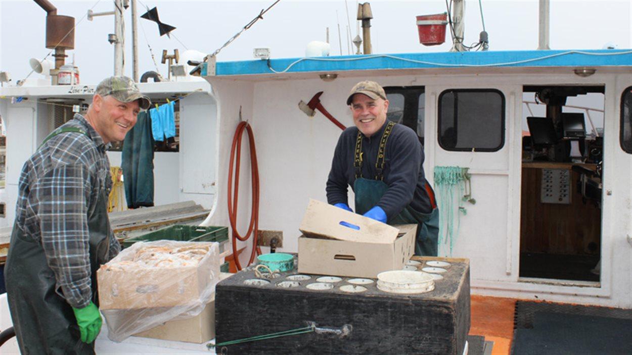 Le pêcheur Claude Cyr, capitaine du homardier le Cap Bleu, en compagnie d'un membre de son équipage.