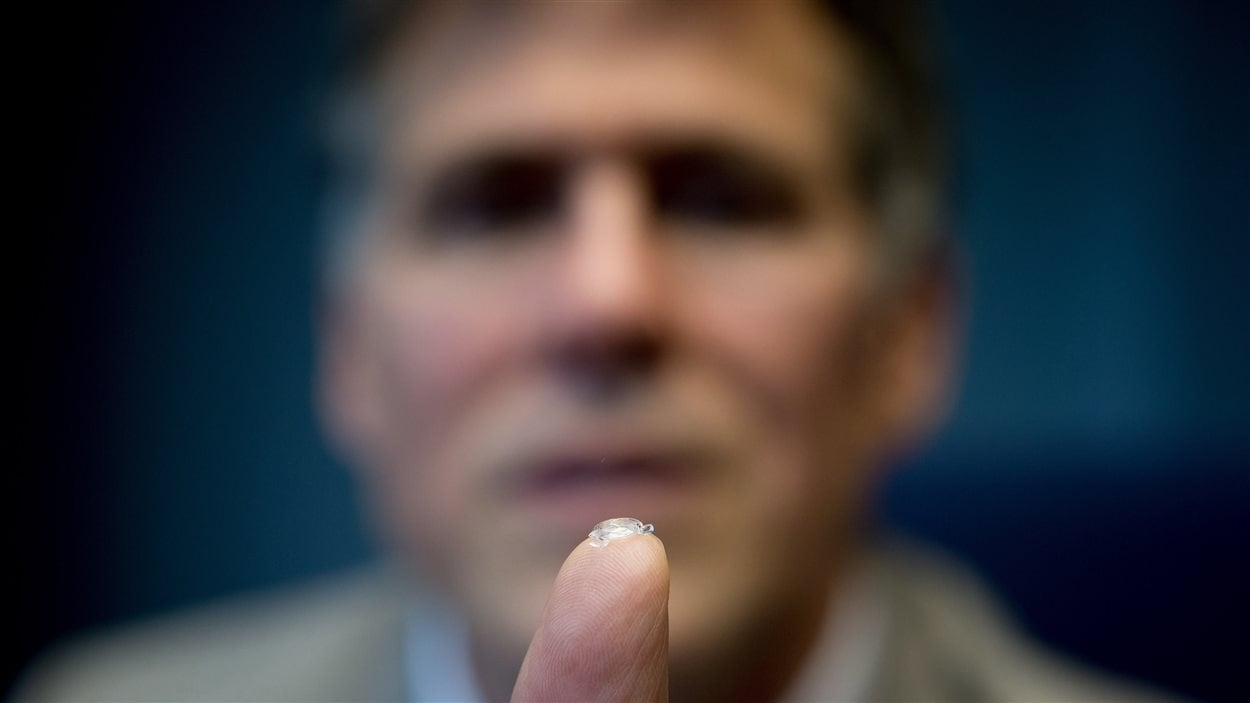 Le Dr Garth Webb montre sa lentille.
