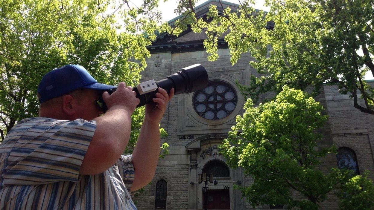 L'ornitologue Richard Dupuis devant l'église Saint-Marc. Le nid se trouve à gauche dans la corniche.