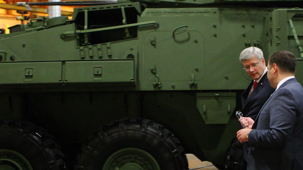 Le premier ministre Stephen Harper, lors d'une visite à l'usine de General Dynamics, en mai 2014. Le véhicule blindé léger qu'on peut y voir était destiné au gouvernement canadien.
