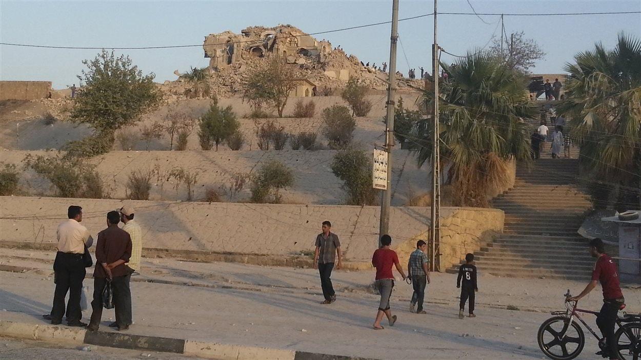 Des passants regardent les ruines de la Mosquée du prophète Jonas, à Mossoul.