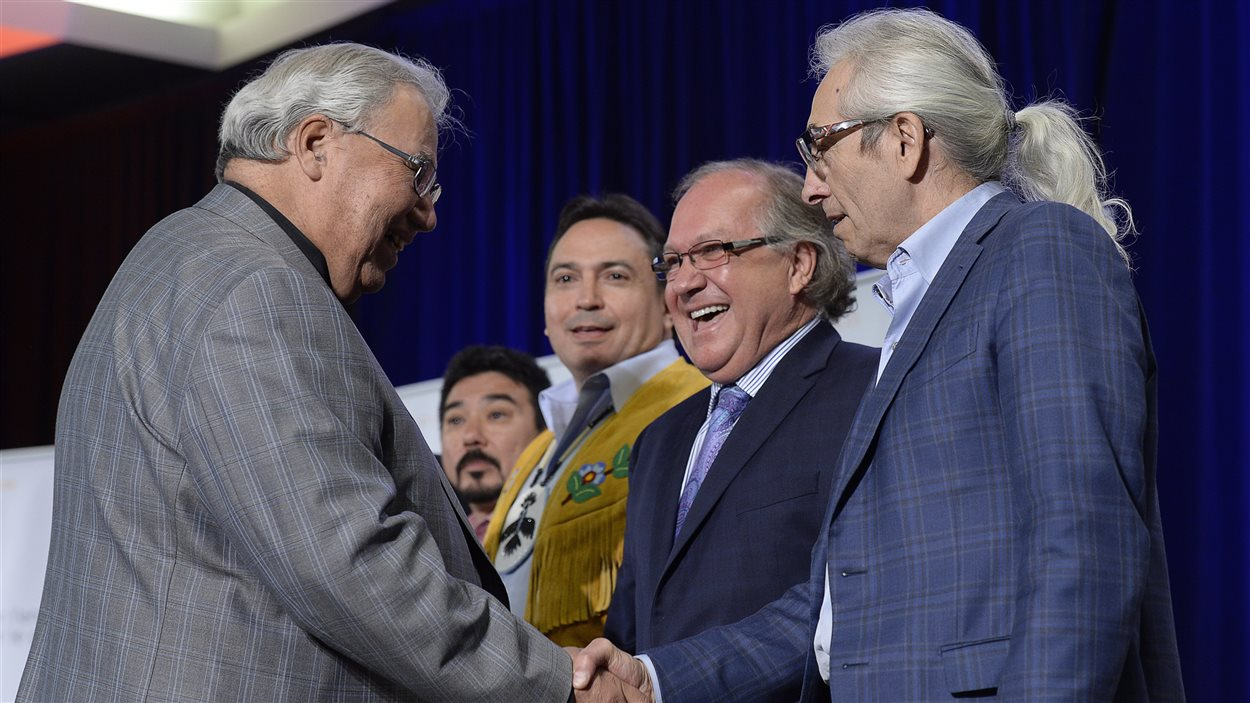 Le président de la Commission de vérité et réconciliation du Canada, le juge Murray Sinclair, serre la main à Phil Fontaine, ex-chef de l'APN. (En arrière-plan, de gauche à droite, le leader inuit Terry Audla, le chef de l'APN, Perry Belgrade, et le ministre des Affaires autochtones, Bernard Valcourt)