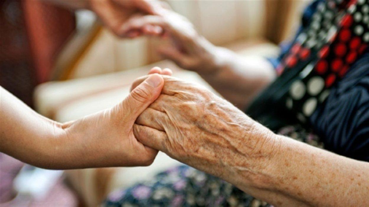Une aînée est tenue par les mains.