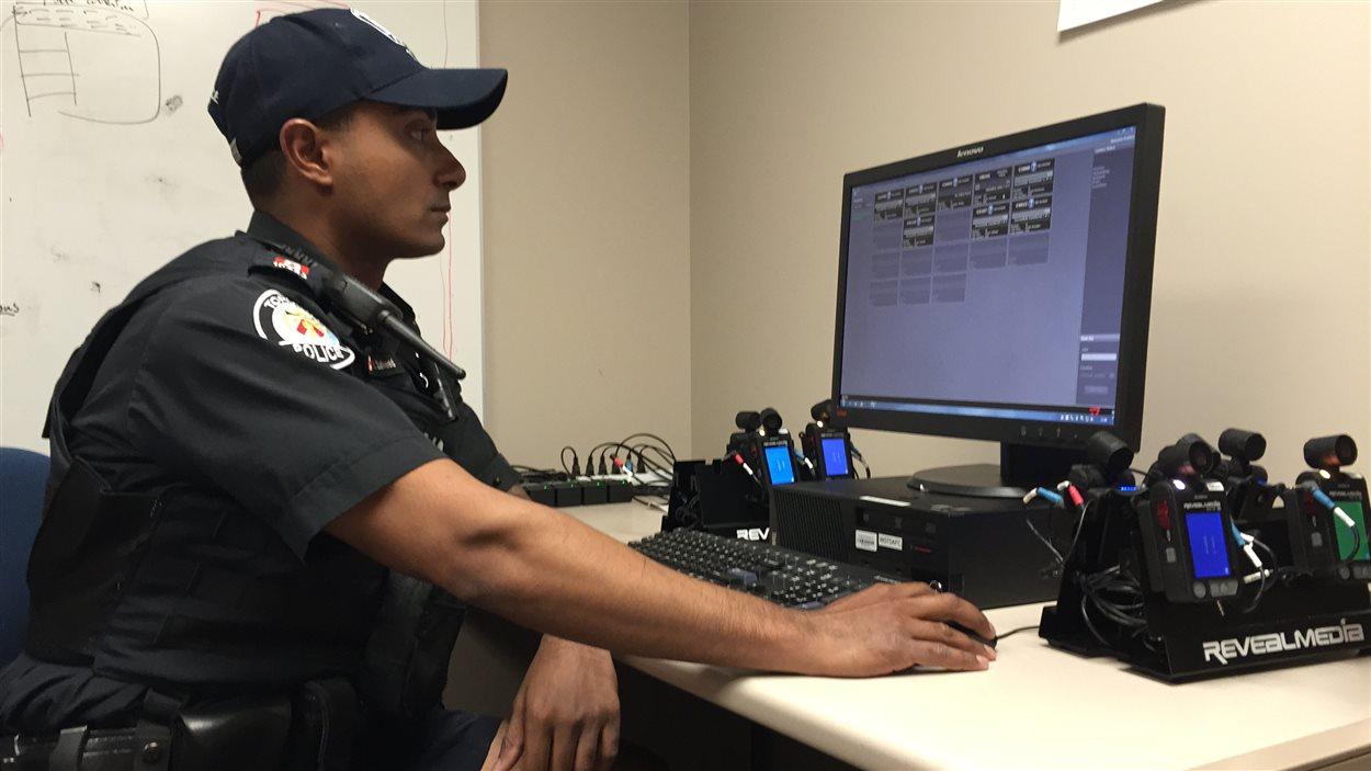 L'agent Ikram Zaheed sauvegarde les vidéos enregistrées avec sa caméra corporelle sur le réseau de la police de Toronto.