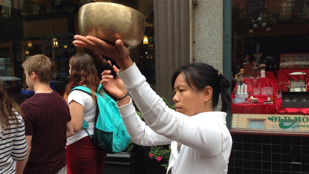 Ela Aquintey, praticienne de méditation holistique, fait résonner le bol tibétain pendant un arrêt lors de la marche silencieuse des élèves à Victoria