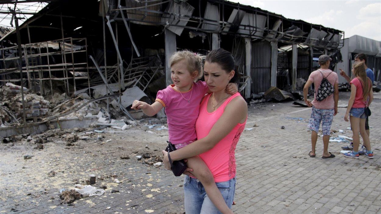 Une femme transportant une fillette marche devant un marché de Donestk endommagé par des bombardements.