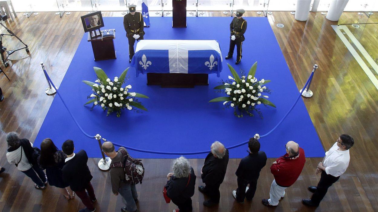 Des gens se recueillent devant le cercueil de Jacques Parizeau.