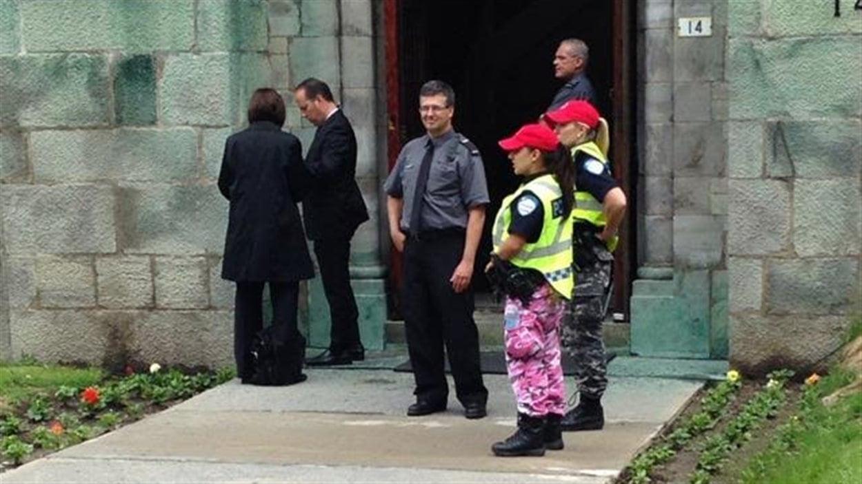 Des agentes du service d'ordre arborent le pantalon de camouflage et la casquette rouge aux funérailles de Jacques Parizeau.