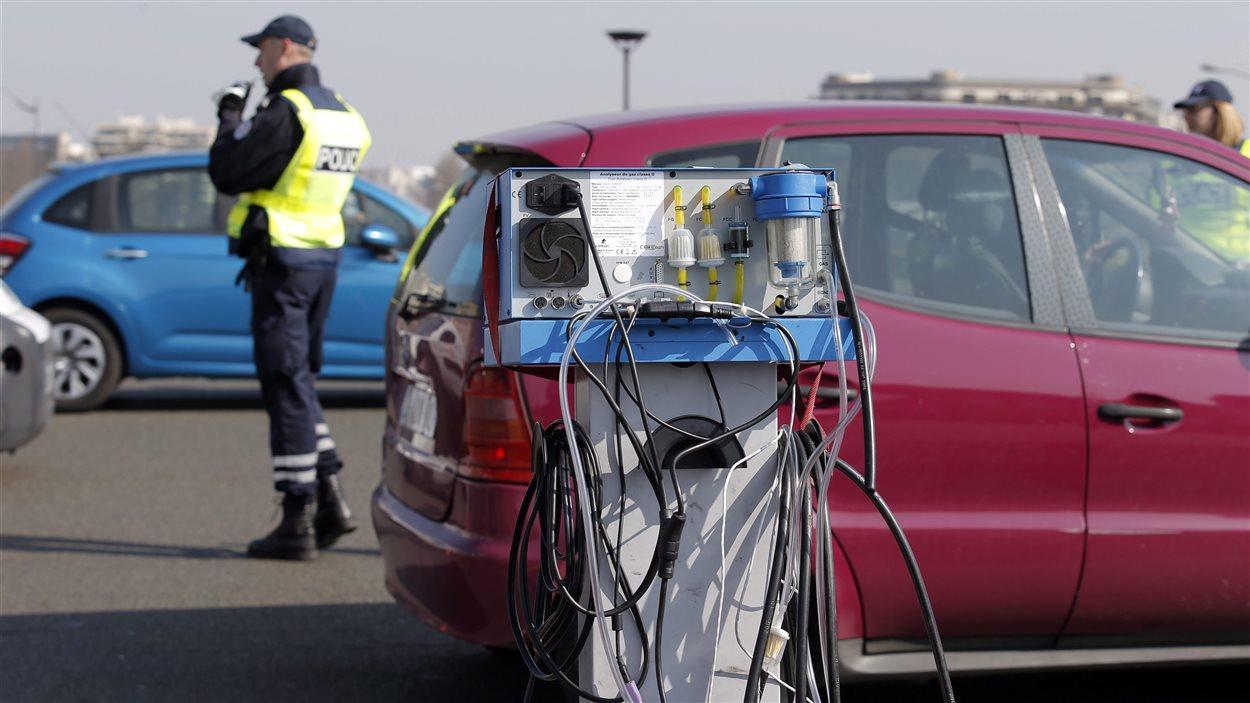 Les policiers parisiens contrôlent le degré de pollution des voitures lors de la journée de circulation alternée en mars 2014