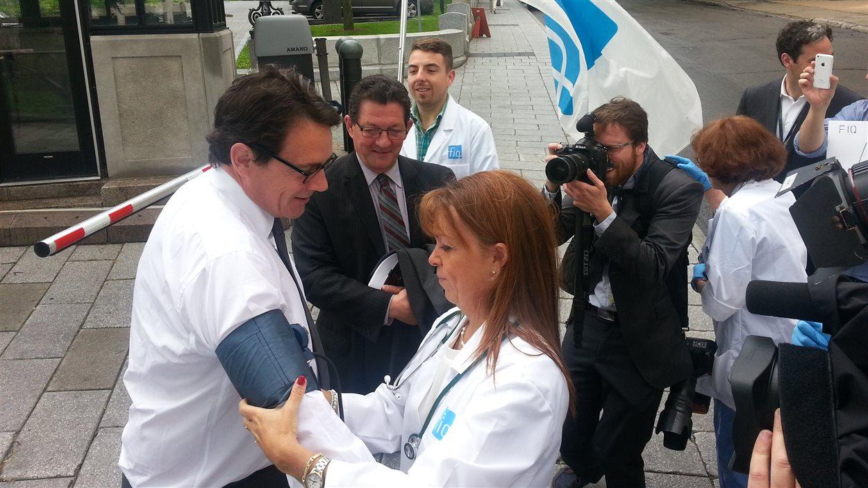 Une infirmière mesure la pression de Pierre Karl Péladeau.