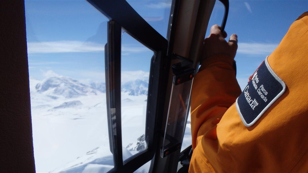manche de l'uniforme d'un secouriste dans un hélicoptère en route vers le mont Logan
