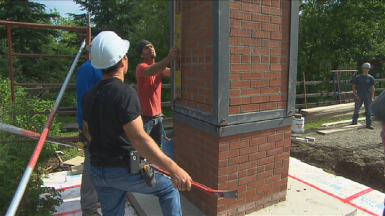 Des élèves du Centre de formation professionnelle 24-Juin construisent une cheminée.